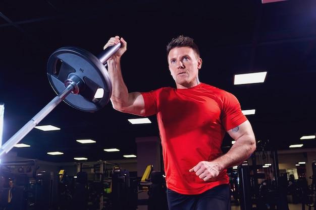 Athletischer männlicher athlet, der übungen mit einem barbell in der turnhalle tut