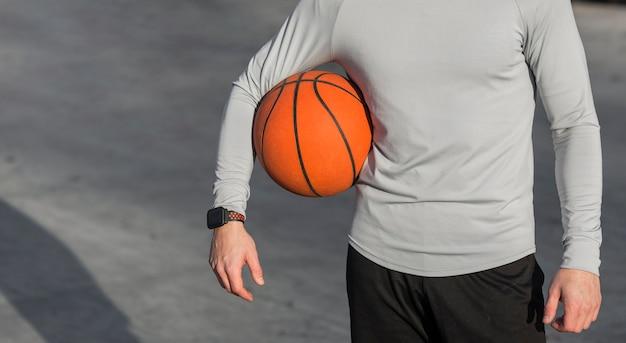 Athletischer männlicher körper und ein basketball