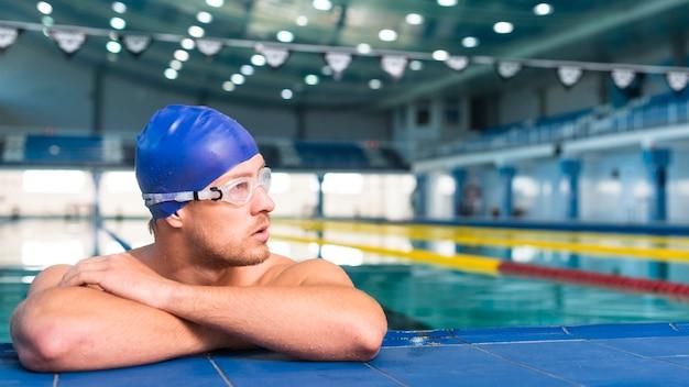 Athletischer männlicher schwimmer, der weg schaut