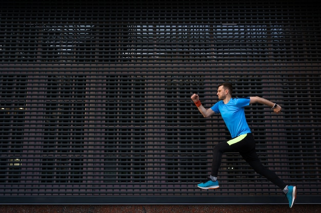 Athletischer mann, der an der städtischen straße gegen grauen hintergrund läuft