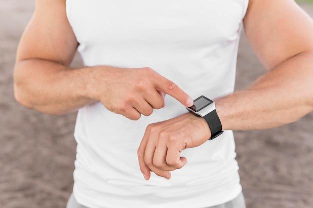Athletischer mann, der auf seine smartwatch zeigt