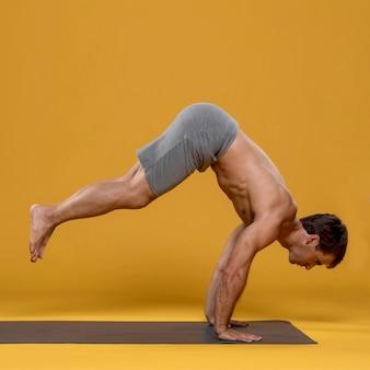 Athletischer mann, der auf yogamatte trainiert