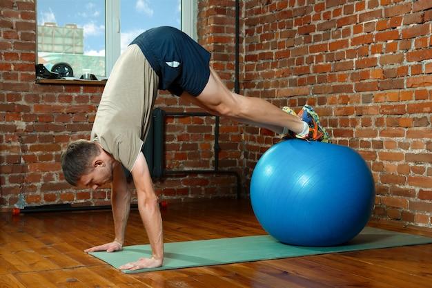 Athletischer mann, der balancierende übungen mit dem turnhallenball tut