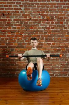 Athletischer mann, der balancierende übungen über dem turnhallenball mit gymnastischem stock tut