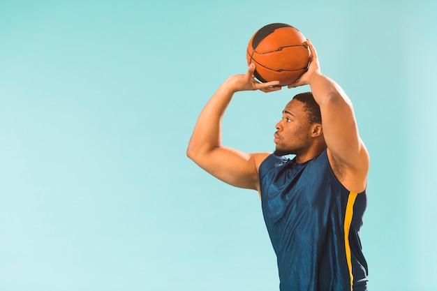 Athletischer mann, der basketball spielt