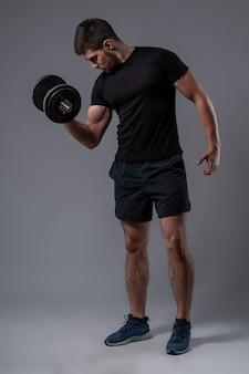 Athletischer mann, der bizepsübung mit hantel durchführt