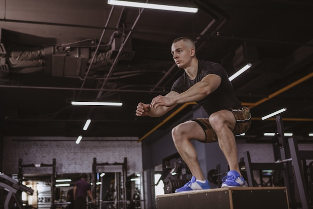 Athletischer mann, der crossfit training am crossfit kasten durchführt