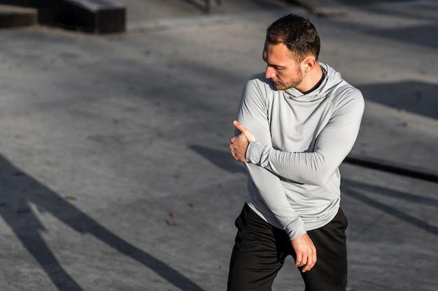 Athletischer mann, der draußen mode aufwirft
