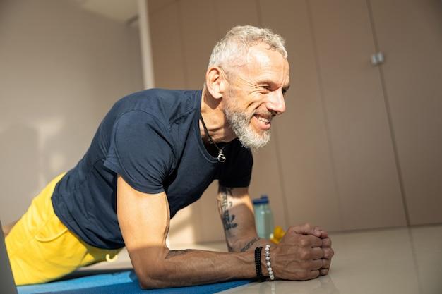 Athletischer mann, der eine planke auf einer blauen abdeckung macht