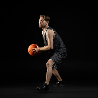 Athletischer mann, der einen basketball hält
