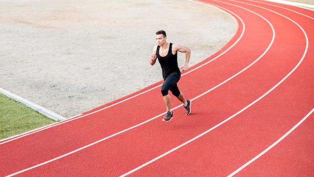 Athletischer mann der männlichen eignung, der auf dem bahnfeld läuft
