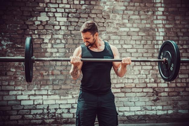Athletischer mann, der mit einem barbell ausarbeitet. kraft und motivation. bizeps-übung.