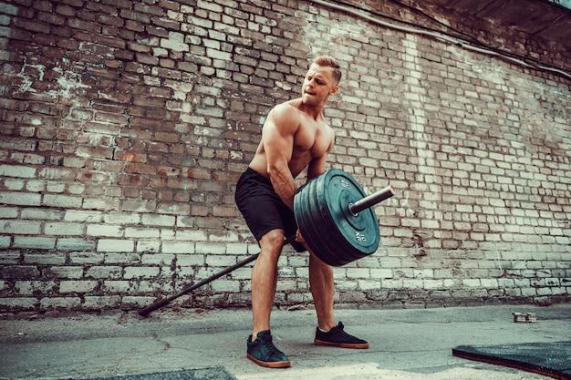 Athletischer mann, der mit einem barbell ausarbeitet. kraft und motivation. übung für die rückenmuskulatur