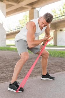 Athletischer mann, der mit einem roten stretchingband arbeitet