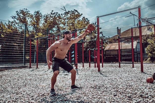 Athletischer mann, der mit einer kettlebell am straßengymnastikhof ausarbeitet