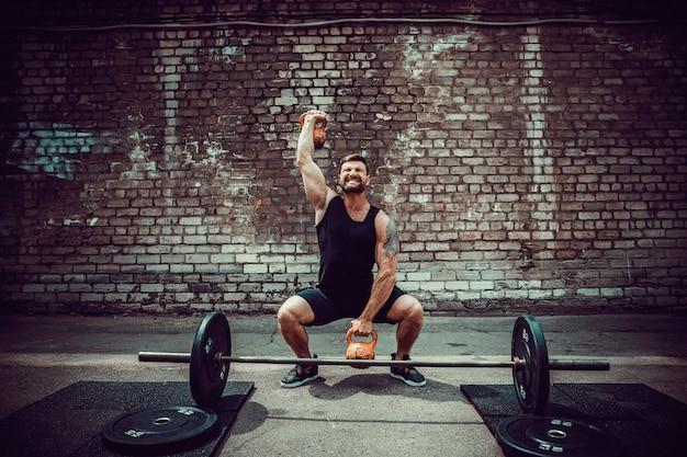 Athletischer mann, der mit einer kettlebell ausarbeitet. kraft und motivation