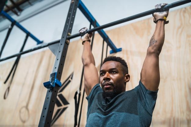 Athletischer mann, der pull-up-übung im fitnessstudio macht.