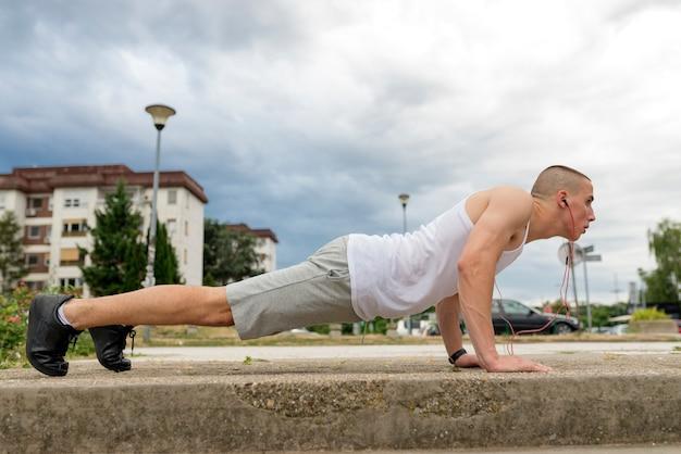 Athletischer mann, der push-up auf einer straße bei sonnenuntergang tut.