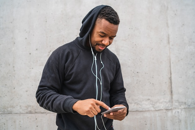 Athletischer mann, der sein telefon verwendet.