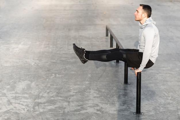 Athletischer mann der seitenansicht, der draußen ausarbeitet