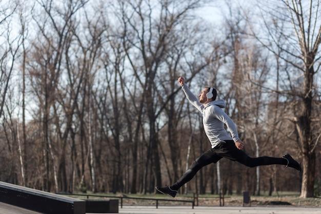 Athletischer mann der seitenansicht, der draußen läuft