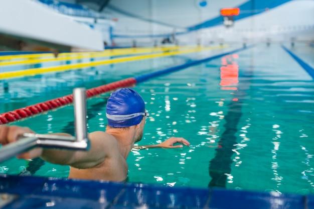 Athletischer mann, der sich vorbereitet zu schwimmen