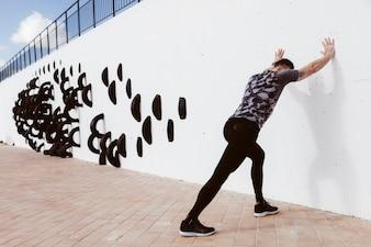 Athletischer Mann, der StoßUPS auf Wand tut