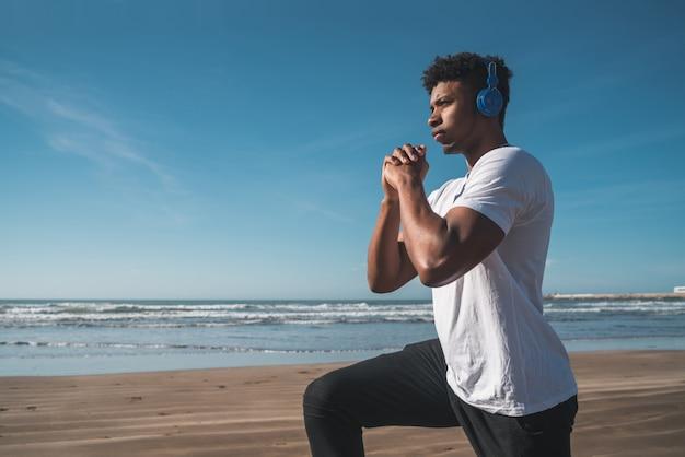 Athletischer mann, der übung am strand tut.