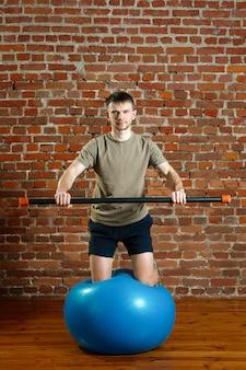 Athletischer mann, der übungen für die balance auf gummiball mit gymnastischem stock tut