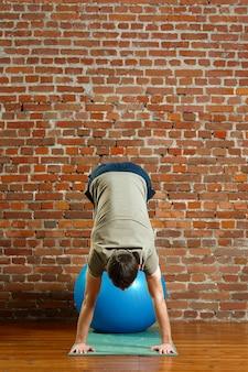 Athletischer mann, der übungen für die balance auf gummiball tut
