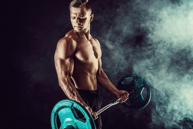Athletischer mann, der übungen mit dummköpfen am bizeps tut. foto des starken mannes mit dem nackten torso auf dunkler wand. kraft und motivation.