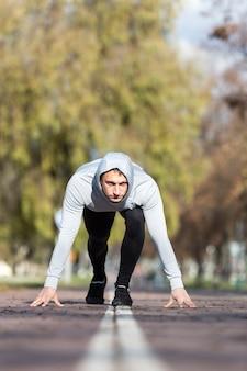 Athletischer mann der vorderansicht, der sich vorbereitet zu laufen