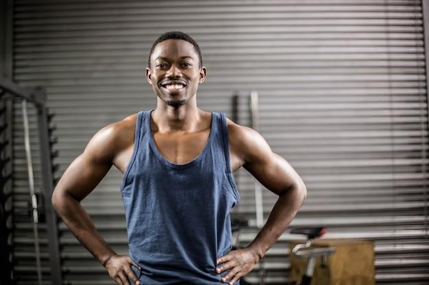 Athletischer mann, der zur kamera an der turnhalle lächelt