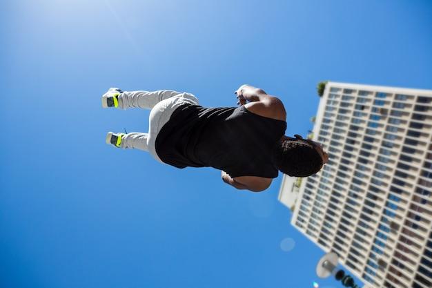 Athletischer mann, der zurück flip in der stadt tut