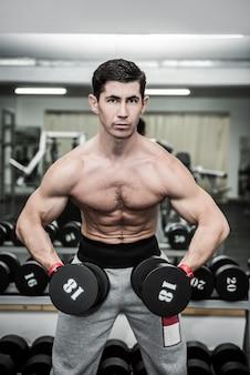 Athletischer mann in der turnhalle, die mit hanteln arbeitet