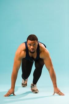 Athletischer mann in der turnhallenausstattung, die sich vorbereitet zu laufen