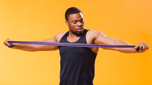Athletischer mann in der turnhallenausstattung, die widerstandband zieht