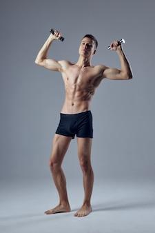 Athletischer mann mit aufgepumptem körper mit hanteln in den händen