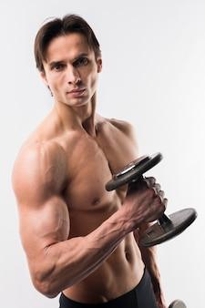 Athletischer mann mit dem körper mit muskeln, der gewichte hält