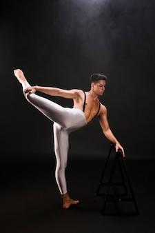 Athletischer mann mit dem nackten torso, der verlängertes bein steht und berührt