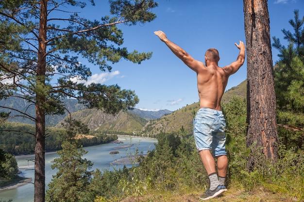 Athletischer mann mit einem bloßen torso und dinosauriershorts breitete aus