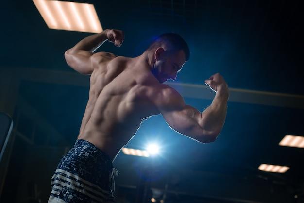 Athletischer mann mit einem muskulösen körper wirft in der turnhalle auf und führt sein bizeps und rückseite vor