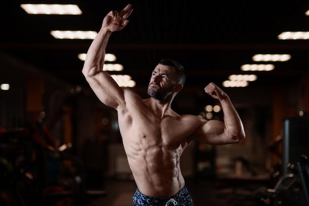 Athletischer mann mit einem muskulösen körper wirft in der turnhalle auf und führt sein bizeps vor. das konzept eines gesunden lebensstils
