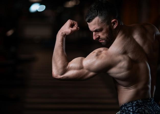 Athletischer mann mit einem muskulösen körper wirft in der turnhalle auf und führt sein bizeps vor