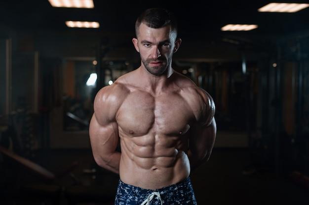 Athletischer mann mit einem muskulösen körper wirft in der turnhalle auf und führt sein musclese vor