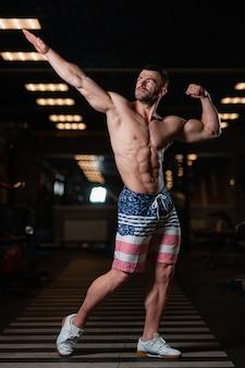 Athletischer mann mit einem muskulösen körper wirft in der turnhalle auf und führt seine muskeln vor. das konzept eines gesunden lebensstils