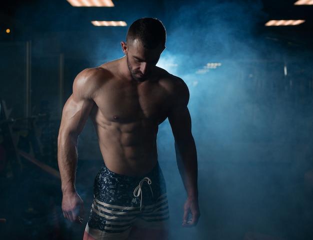 Athletischer mann mit einem muskulösen körper wirft in der turnhalle auf und führt seine muskeln vor.