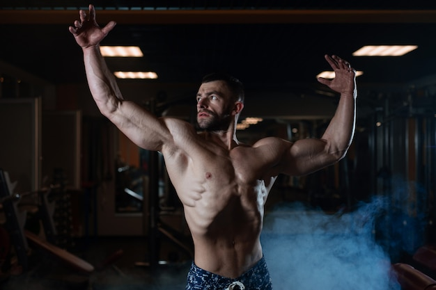 Athletischer mann mit einem muskulösen körper wirft in der turnhalle auf und führt seine muskeln vor