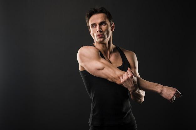 Athletischer mann mit muskeln, der bevor dem trainieren ausdehnt