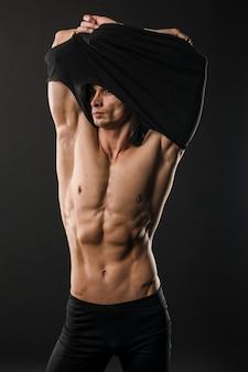 Athletischer mann mit muskeln, der t-shirt entfernt